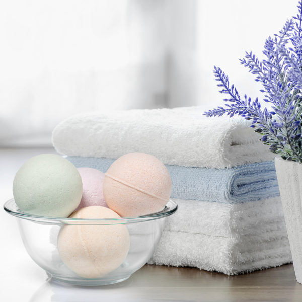 Bath bombs in a bowl next to towels