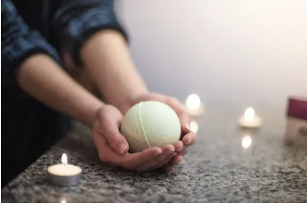 Hands holding bath bomb with candles